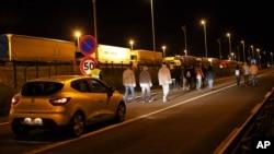 ລົດຮັກສາຄວາມປອດໄພ ອຸໂມງລອດພື້ນທະເລ ຕິດຕາມ ອົບພະຍົບກຸ່ມນື່ງ ທີ່ເຂດ Calais ໃນພາກເໜືອຂອງປະເທດຝຣັ່ງ.