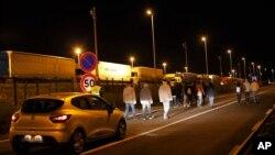 Un automóvil de seguridad de la sociedad del Eurotunnel sigue a un grupo de migrantes, en Calais, norte de Francia, el miércoles, 29 de julio, de 2015.