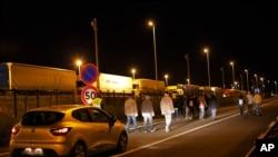 Un véhicule de sécurité de la société Eurotunnel avance derrière un groupe de migrants, à Calais, dans le nord de la France, le 29 juillet 2015.