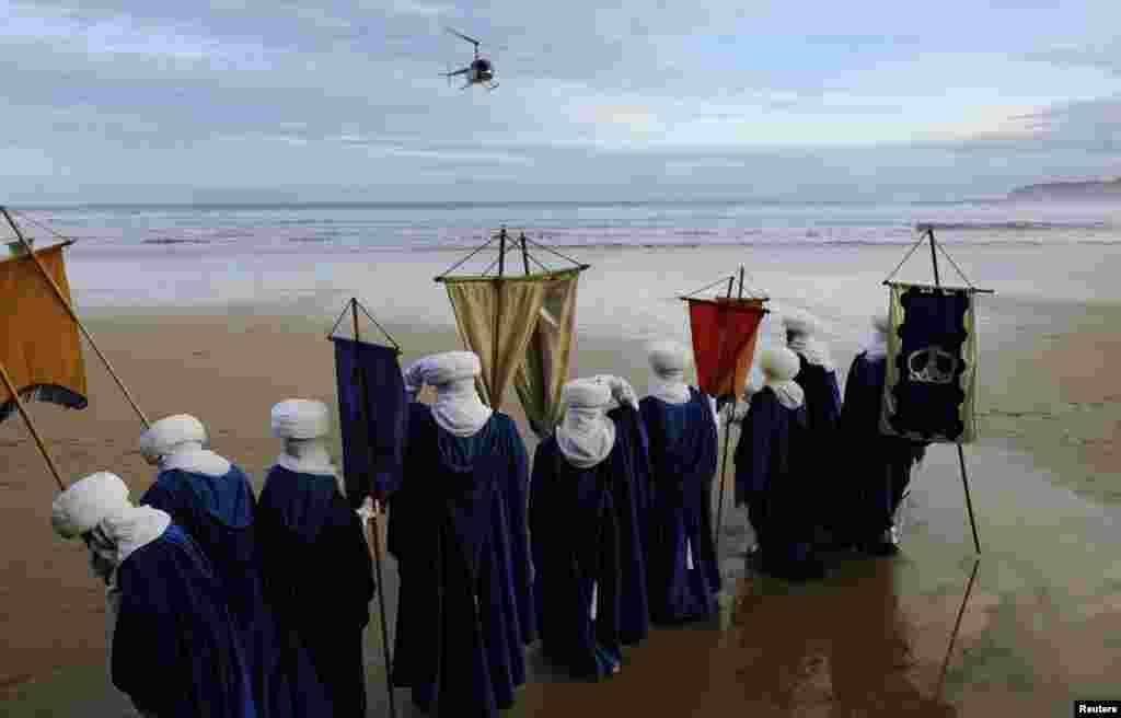 People role playing as members of the royal entourage await the arrival of the Three Wise Men by helicopter, at San Lorenzo beach in Gijon.Children in Spain traditionally receive their Christmas presents on the morning of Jan. 6, delivered by the Three Wise Men.
