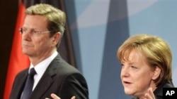 ນາຍົກລັດຖະມົນຕີ Angela Merkel ແຫ່ງເຢຍຣະມັນ ຢືນຢູ່ຂ້າງຂວາ ຮອງນາຍົກ Guido Westerwelle ວັນທີ 12 ມີນາ 2011
