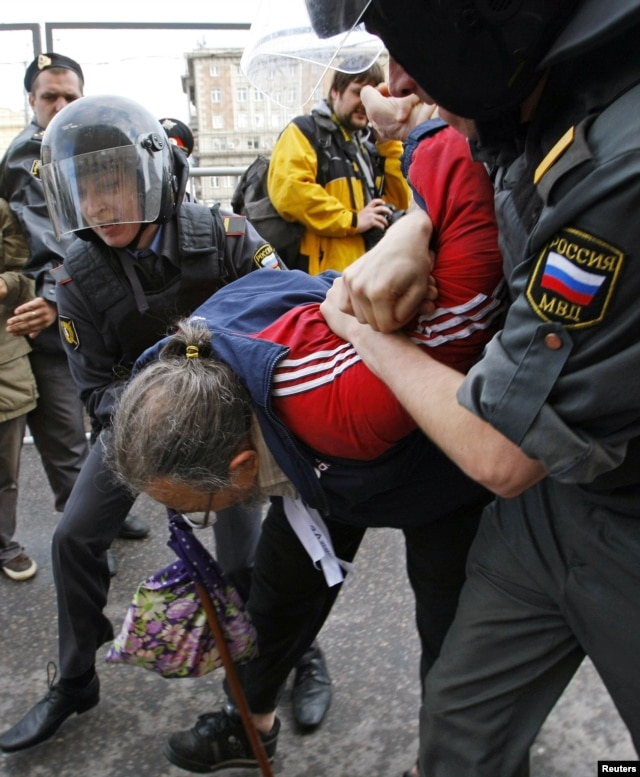 Russian police detain an opposition activist, with the white ribbon as a symbol of protest, during an anti-Kremlin protest in Moscow, May 31, 2012.