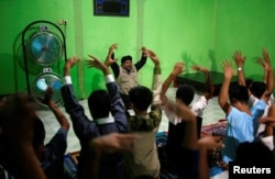 Recovering drug addicts and staff at a traditional rehabilitation center participate in physical activity during a prayer session led by Ustad Ahmad Ischsan Maulana in Purbalingga, Central Java, Indonesia, July 27, 2016. The center claims to have treated hundreds of addicts with a routine of herbal teas, baths, prayer and counseling.