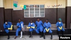 Health workers rest outside a quarantine zone at a Red Cross facility in the town of Koidu, Kono district in Eastern Sierra Leone December 19, 2014. (REUTERS/Baz Ratner)