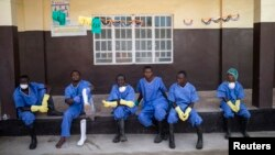 FILE - Health workers rest outside a quarantine zone at a Red Cross facility in the town of Koidu, Kono district in eastern Sierra Leone, Dec. 19, 2014.