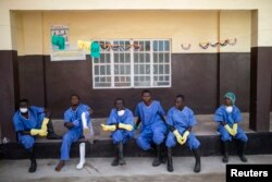 Health care workers rest outside a Red Cross facility in the town of Koidu in eastern Sierra Leone, Dec. 19, 2014.