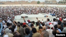 FILE - People gather around an ambulance carrying the coffin of Awami National Party (ANP) candidate Haroon Bilour, who was among those killed in a suicide attack during a July 10 election campaign meeting, in Peshawar, Pakistan, July 11, 2018.