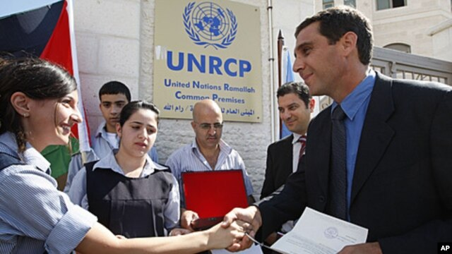 A Palestinian school girl, left, hands a letter, addressed to the United Nations Secretary-General Ban Ki-moon, to UN officer Pascale Soto, right, during a rally to support the Palestinian statehood bid in the United Nations, in the West Bank city of Rama