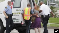 Police arrest a protester after she refused to leave the area during an attempt to shut down Interstate 70 near the St. Louis suburb of Ferguson, Missouri, where Michael Brown, an unarmed, black 18-year old was shot and killed by a white police officer on