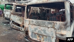 FILE - Burned buses are seen at the bus terminal in Buea, Cameroon, after gunfire broke out, July 9, 2018.