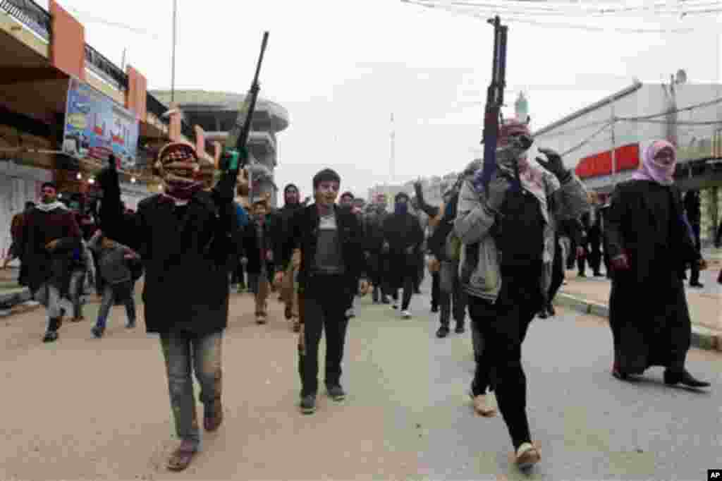 Mourners and Sunni gunmen chant slogans against Iraq's Shiite-led government during funeral of a man killed in clashes in Fallujah, Jan. 4, 2014.