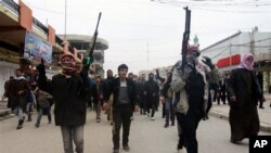 Mourners, Sunni gunmen chant slogans against Iraq's Shiite-led government during funeral of a man killed in clashes between al-Qaida gunmen, Iraqi troops, Fallujah, Jan. 4, 2014.