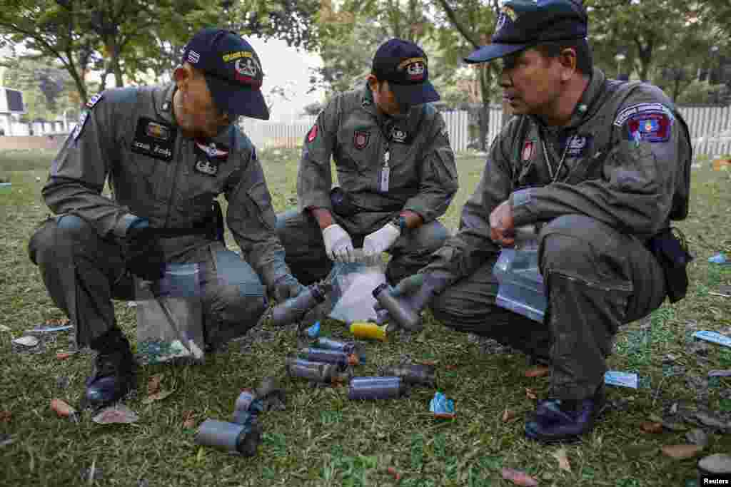 Thai security personnel inspect unidentified objects at the Thai-Japan youth stadium, the site of fierce clashes between anti-government protesters and riot police, in central Bangkok, Thailand, Dec. 27, 2013.