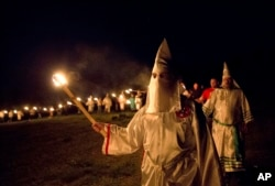 "In this Saturday, April 23, 2016 photo, members of the Ku Klux Klan participate in cross burnings after a ""white pride"" rally in rural Paulding County near Cedar Town, Ga."