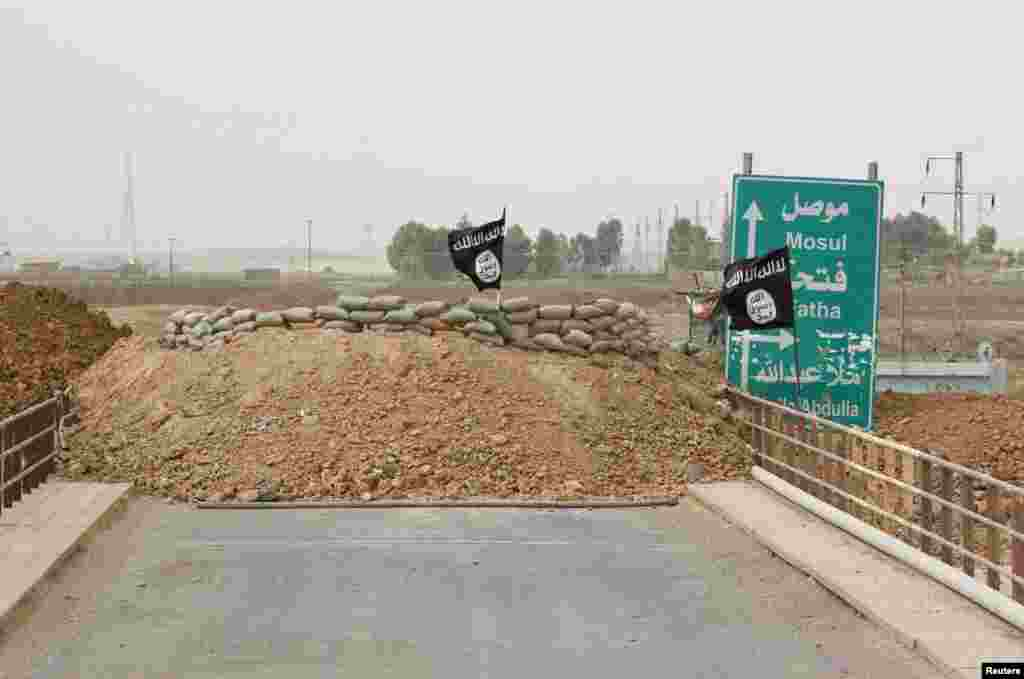 Islamic State flags flutter on the Mullah Abdullah bridge where members of the Kurdish security forces and the Islamic State are holding fort behind sandbags on different ends of the bridge, in southern Kirkuk, Sept. 29, 2014.