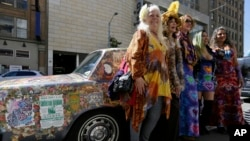 Women stand next to a psychedelic Rolls Royce at the California Historical Society in San Francisco.The car belongs to Donna Huggins (second from left) and is covered with original music posters and artwork from 1967. (AP Photo/Eric Risberg)