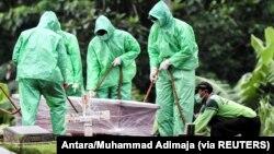 Para pekerja bersiap untuk menguburkan seorang korban yang meninggal akibat COVID-19 di area pemakaman Pondok Ranggon di Jakarta, 30 Maret 2020. (Foto: Antara/Muhammad Adimaja via Reuters)