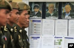 Cambodian military officials line up in front the top leaders of Khmer Rouge portraits, from right, former Khmer Rouge Foreign Minister Ieng Sary, former Khmer Rouge head of state Khieu Samphan, and former Deputy Secretary Nuon Chea, during the second day of trial of the U.N.-backed war crimes tribunal in Phnom Penh, Cambodia, Tuesday, Dec. 6, 2011.
