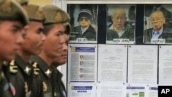 Cambodian military officials line up in front the top leaders of Khmer Rouge portraits, from right, former Khmer Rouge Foreign Minister Ieng Sary, former Khmer Rouge head of state Khieu Samphan, and former Deputy Secretary Nuon Chea, during the second day of trial of the U.N.-backed war crimes tribunal in Phnom Penh, Cambodia, Tuesday, Dec. 6, 2011. Three senior leaders of Cambodia's brutal Khmer Rouge regime on Tuesday continue to be questioned at the U.N.-backed tribunal over their roles in the deaths of an estimated 1.7 million people when their movement held power in the 1970s.