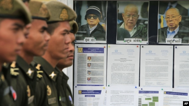 Cambodian military officials line up in front the top leaders of Khmer Rouge portraits, from right,  former Khmer Rouge Foreign Minister Ieng Sary, former Khmer Rouge head of state Khieu Samphan, and  former Deputy Secretary Nuon Chea, during the second day of trial of the U.N.-backed war crimes tribunal in Phnom Penh, Cambodia, Tuesday, Dec. 6, 2011. Three senior leaders of Cambodia's brutal Khmer Rouge regime on Tuesday continue to be questioned at the U.N.-backed tribunal over their roles in the deaths of an estimated 1.7 million people when their movement held power in the 1970s. (AP Photo/Heng Sinith)