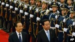 日本首相野田佳彦(右)和中国总理温家宝12月25日在北京人民大会堂举行的欢迎仪式上检阅仪仗队