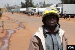 Boda boda driver Keneth Owuma shows off his new helmet, Kampala, Uganda, August 28, 2013. (Hilary Heuler for VOA)