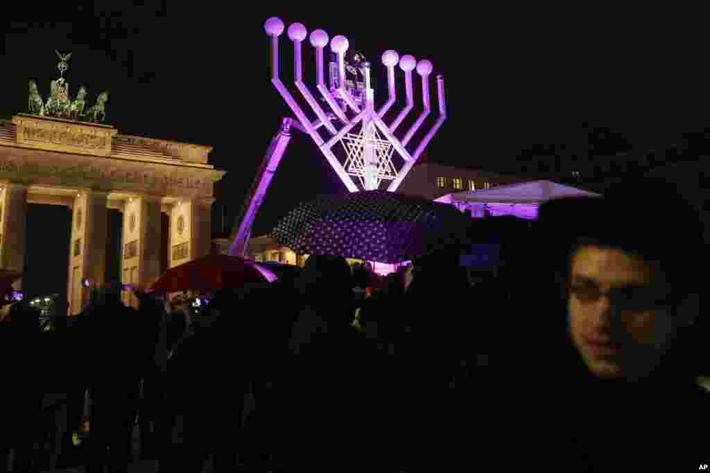 A giant Hanukkah Menorah set up by the Jewish Chabad Educational Center, is illuminated at the Pariser Platz in front of the Brandenburg Gate in Berlin, Tuesday, Dec. 12, 2017. (AP Photo/Markus Schreiber)