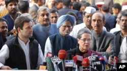 India's Congress Party President Sonia Gandhi, front, and her son and party Vice President Rahul Gandhi, left, addresses the media about her corruption accusation in New Delhi, India, Dec. 19, 2015. The Gandhis deny the allegations.