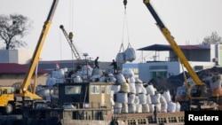一只中国边境贸易的货船停泊在朝鲜新义州的岸边,正在卸货(资料照片)