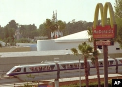 The monorail, which encircles Disneyland in Anaheim, Calif., makes its way past a McDonald's restaurant outside the amusement park Thursday, May 23, 1996.