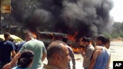 In this photo released by the Syrian official news agency SANA, Syrians gather at the site of a car bombing in the port city of Latakia, Syria, Sept. 2, 2015.