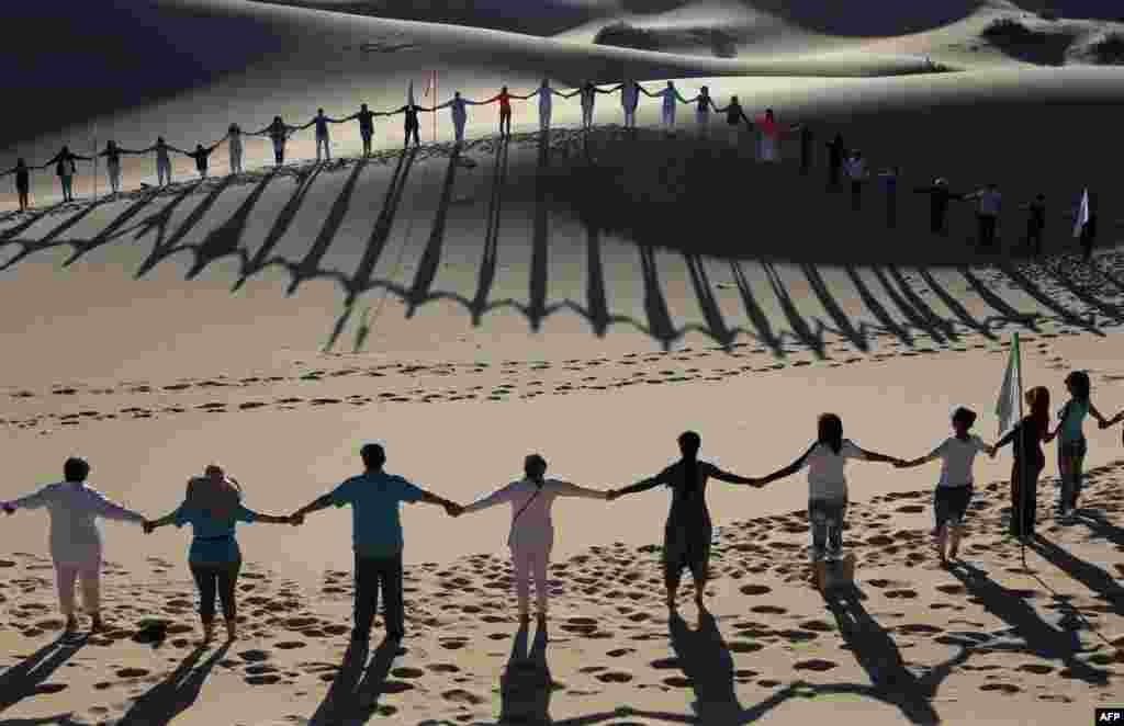 មនុស្សម្នាចូលរួមថ្នាក់ហាត់យូហ្គា នៅក្នុងកម្មវិធីរៀបចំដោយសហគមន៍ YSYoga System នៅទីវាល Samalayuca Dune Fields ក្នុងក្រុង Juarez រដ្ឋ Chihuahua ប្រទេសម៉ិកស៊ិក កាលពីថ្ងៃទី២៥ ខែឧសភា ឆ្នាំ២០១៩។