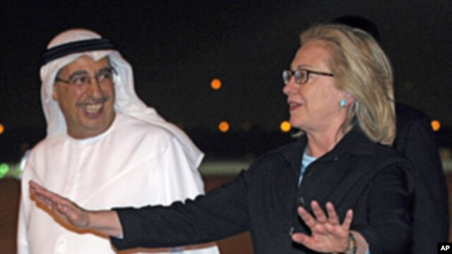 Secretary of State Hillary Rodham Clinton (r) is greeted by UAE Assistant Foreign Minister for Political Affairs Tareq Al-Haidan, upon her arrival at the airport in Abu Dhabi,  June 8, 2011