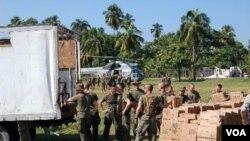 Tropas estadounidenses descargan alimentos para un orfanato destruido por el terremoto.