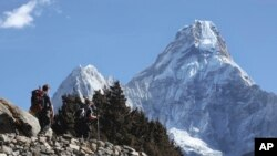 FILE - Trekkers make their way to Dingboche, a popular Mount Everest base camp, in Pangboche, Nepal, Feb. 19, 2016.