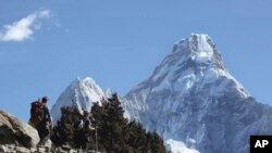 FILE - Trekkers make their way to Dingboche, a popular Mount Everest base camp, in Pangboche, Nepal, Feb. 19, 2016. Officials say three foreign climbers along with three Nepalese guides have scaled Mount Everest, the first foreigners to reach the summit in two years.