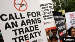 Activists campaigning for a global arms trade treaty hold placards during a protest in New Delhi, India, Sept. 13, 2006.