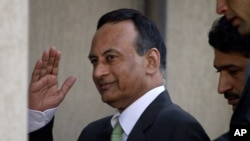 Pakistan's former ambassador to the U.S., Husain Haqqani, salutes to media as he arrive to appear before a judicial commission at high court in Islamabad, Pakistan, January 9, 2012.