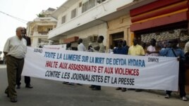 "A group of 50 people hold a banner reading ""Shed light on the death of Deyda Hydara. Stop assassinations and violence against journalists and the press,"" during a protest in front of Gambia's high commission, 22 December 2004 in Dakar."