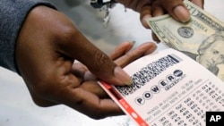 FILE - A clerk hands over a Powerball ticket for cash at Tower City Lottery Stop in Cleveland, Jan. 13, 2016. One ticket matched Saturday's winning numbers for a nearly $430 million jackpot.
