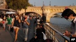 ျပင္သစ္ႏုိင္ငံ ပဲရစ္ၿမိဳ႕က Seine ျမစ္ကမ္းေဘးမွာ ႏွာေခါင္းစည္းတပ္ သြားလာေနၾကသူမ်ား။ (စက္တင္ဘာ ၁၁၊ ၂၀၂၀)