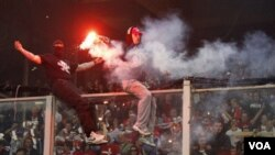 Pendukung Serbia menaiki pembatas untuk melempar petasan dan kembang api ke lapangan dalam pertandingan kualifikasi Euro 2012 grup C antara Italia dan Serbia di Genoa hari Selasa (12/10).