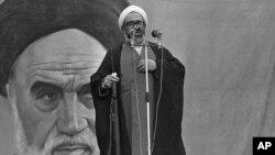 آیت الله حسینعلی منتظری، درحالی که تفنگ در دست دارد و جلوی تصویر آیت الله خمینی ایستاده، برای جمعیت بزرگی در دانشگاه تهران سخنرانی می کند. جمعه، ۲ آذر ۱۳۵۸