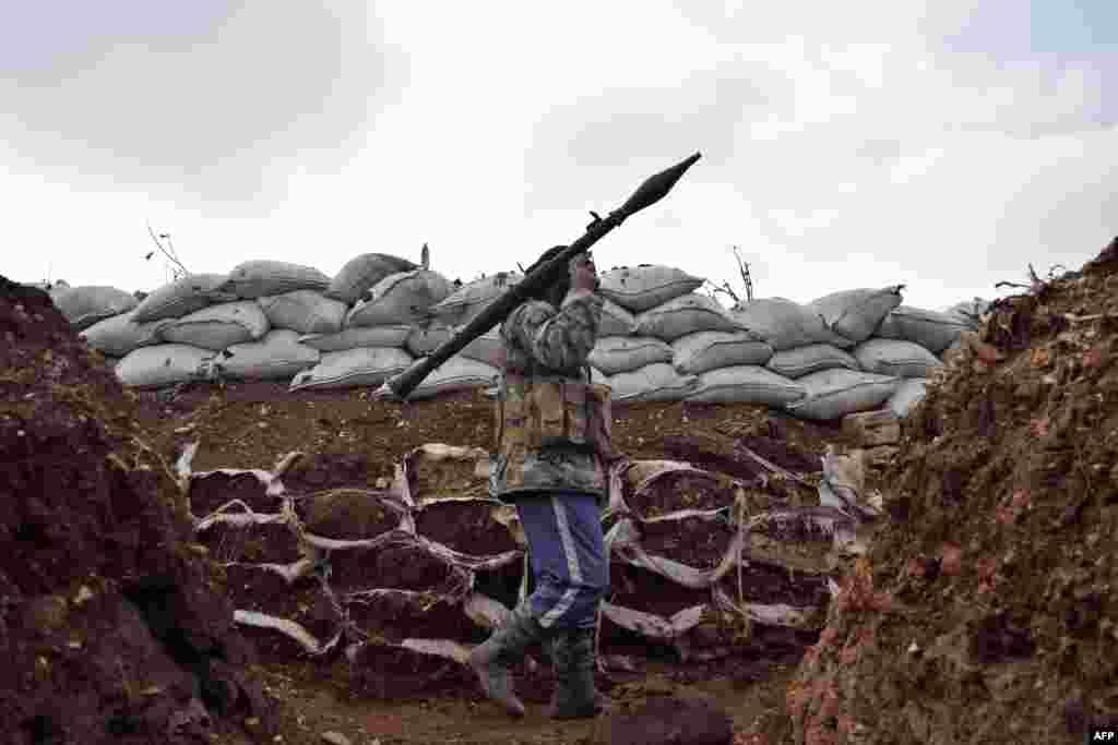 Combatente do grupo da oposição síria Brigada Sham durante confrontos com forças governamentais perto de Homs.