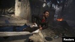 Un homme transporte un corps après un bombardement à Douma, en Syrie, le 7 novembre 2015.