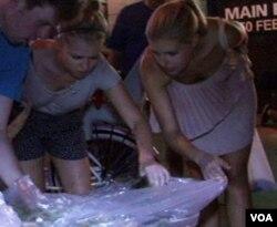 Alicia dan Isabelle membuka plastik sampah dan mencari makanan yang masih bisa diselamatkan di depan sebuah supermarket.