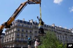 بے بی مجسمہ آزادی کو فرانس سے امریکہ بھیجنے کے لیے کرین کی مدد سے اٹھایا جا رہا ہے۔ فوٹو اے پی
