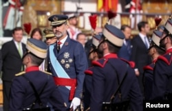Spain's King Felipe reviews the guard during a military parade marking Spain's National Day in Madrid, Oct. 12, 2017.
