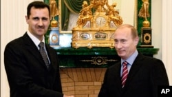 FILE - In this Dec. 19, 2006 file photo Vladimir Putin, then Russian President, right, and his Syrian counterpart Bashar Assad smile as they shake hands in Moscow's Kremlin.