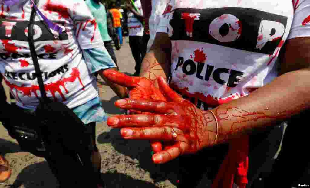 Un membre de la société civile a enduit ses mains de faux sang et chante des slogans lors de la manifestation contre les meurtres extrajudiciaires après le meurtre de Willie Kimani, avocat et défenseur des droits de l'homme, à Nairobi, Kenya le 4 juillet. Lire la suite ici.